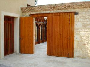 Portail en bois d'entrée extérieure à 2 vantaux avec un vantail ouvert sur un patio